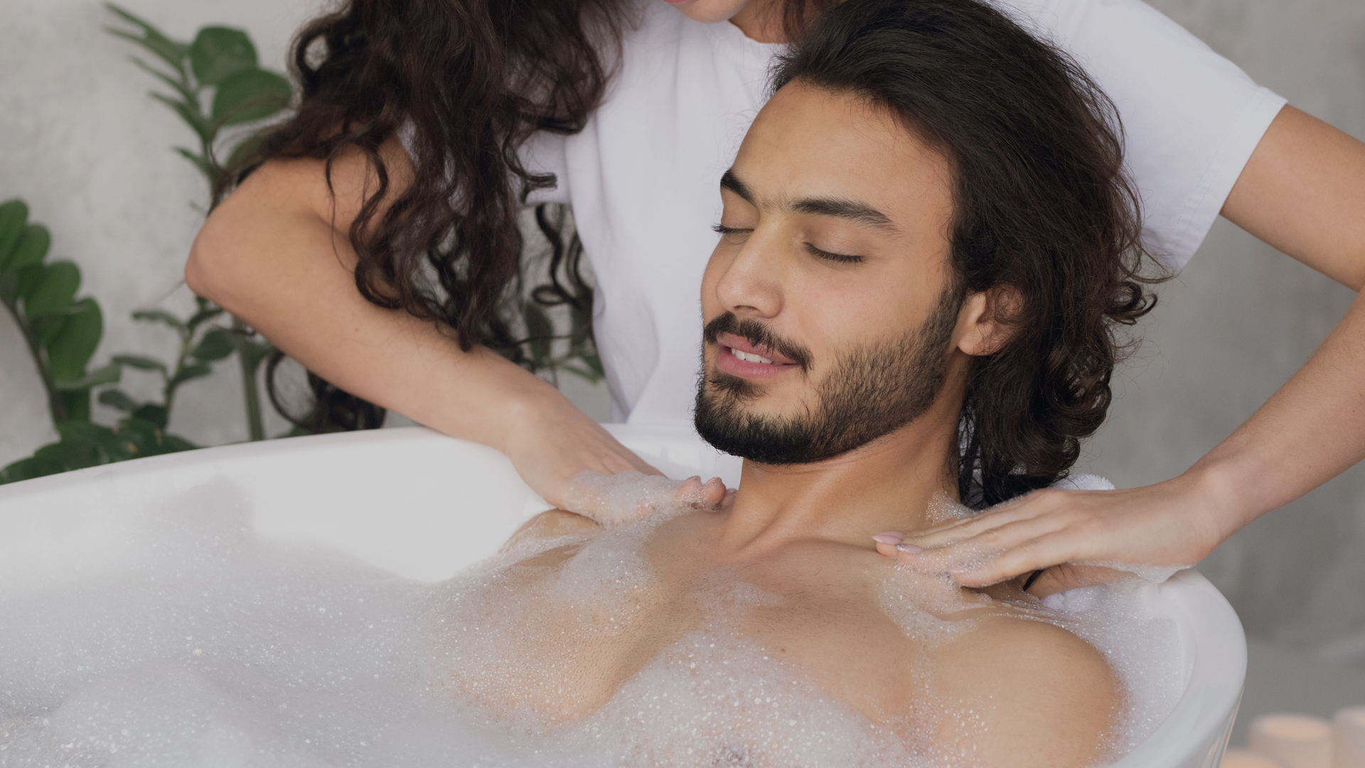Pretty young woman making massage to her husband enjoying hot bath with foam